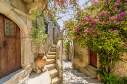Fancy flower decorated narrow sunny street with stairs in old town in summer sunshine, Sicily, Italy