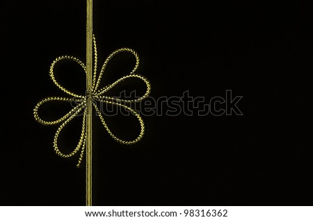Fancy gold yellow ribbon bow isolated on black background with room for your text