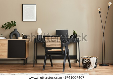 Fancy interior design of home office space with stylish chair, desk, commode, black mock up poster frame, lapatop, book, desk organizer and elegant presonal accessories in home decor. Template.