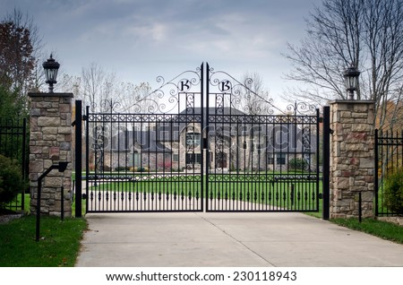 fancy large mansion behind a locked gate