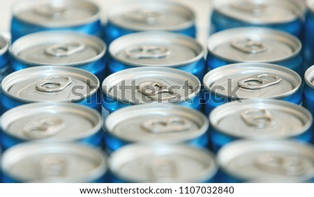 Photo of Fancy metal cans with refreshing drinks, in macro picture. Loads of unopened soda or beer cans. Cylindrical metal containers. Canned drinks in a row.