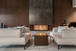Fancy modern room with a burning fireplace, wooden wall and a tiled floor. There is a glossy table with sofas with pillows, glass stand with vases, black bag with firewood, speaker. Horizontal.
