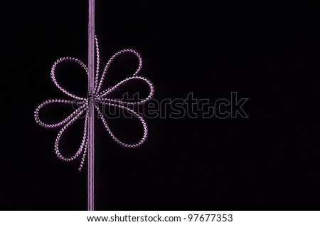 Fancy purple ribbon bow isolated on black background with room for your text