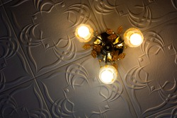 Fancy shining chandelier  decorated with glass patterns in the form of autumn leaves, hanging from the ceiling decorated with patterned tiles with three light bulbs shining in darkness. Vignetted