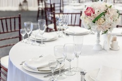 Fancy table set for dinner with flower composition in restaurant, luxury interior background. Wedding elegant banquet decoration and items for food arranged by catering service on white table