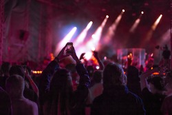 fans at a music concert dance and shoot video on the phone, youth outdoor festival