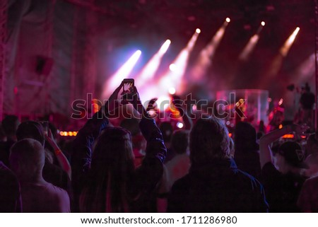 fans at a music concert dance and shoot video on the phone, youth outdoor festival Foto stock ©