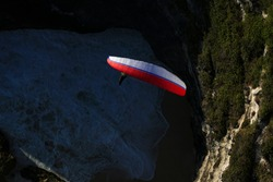 Fans of extreme paragliding, flying over the cliffs of Melasti beach, Bali.