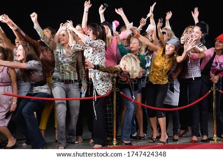 Fans screaming and cheering behind velvet rope Сток-фото ©