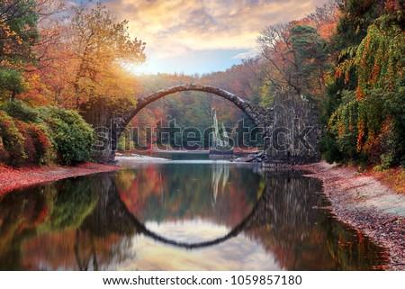 Fantastic Autumn Landscape. Amazing sunset With colorful sky in Azalea and Rhododendron Park Kromlau .Rakotz Bridge, Rakotzbrucke Devil's Bridge in Kromlau, Saxony, Germany. Creative Artistic image.  Сток-фото ©