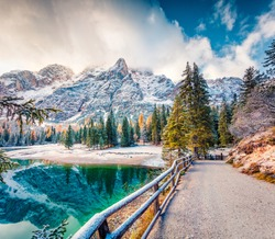 Fantastic autumn view of Braies Lake. First snow in mountains. Colorful morning sunrise of Dolomite Alps, Naturpark Fanes-Sennes-Prags, Italy, Europe. Beauty of nature concept background.