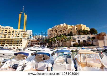 Fantastic city landscape on the seaside with boats. Portomaso Business Tower, Malta.