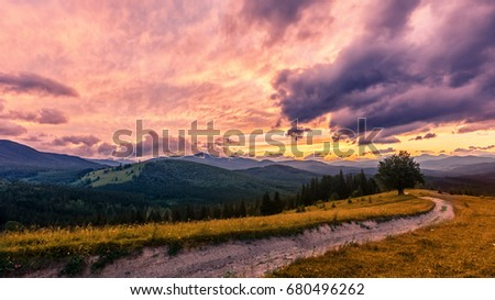 fantastic colorful landscape. overcast clouds glowing in sunlight over the mountain meadow foreground dirt road. picturesque nature view. dramatic scene. artistic creative image. retro vintage style #680496262