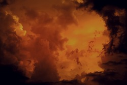Fantastic concept mystical horror background from another planet from the paranormal world, fantasy style. Dramatic red black orange sky with scary hellish clouds and terrible shadows and light