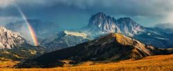 Fantastic dramatic view on Dolomites Alps. Italy. Wonderful nature landscape. Scenic image of Mountain valley with majestic mountains, overcast sky and rainbow during sunset. great natural background
