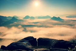Fantastic dreamy sunrise on top of rocky mountain with view into misty valley.Mountain view.Foggy mountain.Dreamy forrest. Sunrise clouds. Forest hill.Autumn mist.Misty peaks.Foggy landscape. Hill top