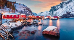 Fantastic evening cityscape of Nusfjord town, Norway, Europe. Great sunset on Lofoten Island archipelago. Fabulous winter seascape of Norwegian sea.  Life over polar circle.