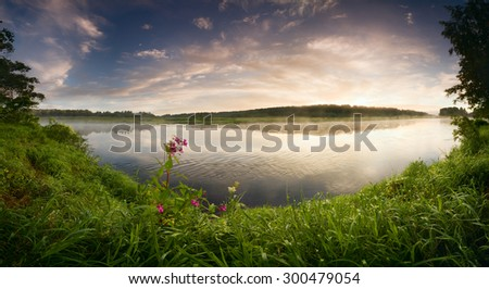 Fantastic foggy river with flowers and fresh green grass in the sunlight. Sun beams through tree. Dramatic colorful scenery, Russia. Beauty world.