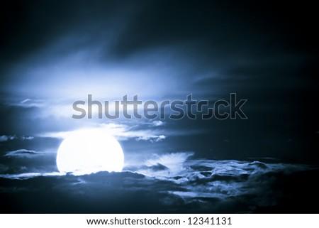 Fantastic glowing moon bathing in a dark blue night sky