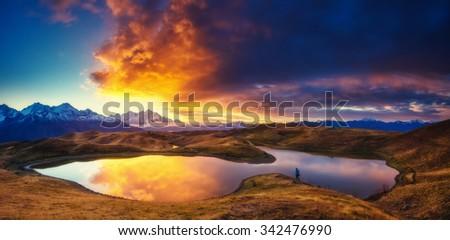 Fantastic lake Koruldi with overcast sky at the foot of Mt. Ushba. Dramatic morning scene. Upper Svaneti, Mestia, Georgia, Europe. High Caucasus ridge. Warm toning effect. Beauty world.