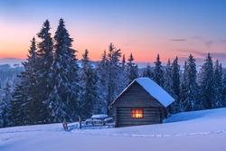 Fantastic landscape glowing by sunlight. Dramatic wintry scene with snowy house. Carpathians, Ukraine, Europe.