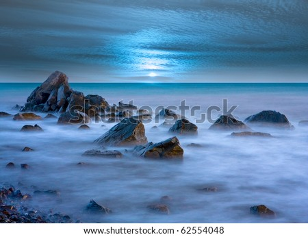fantastic landscape with stones in sea water in dusk