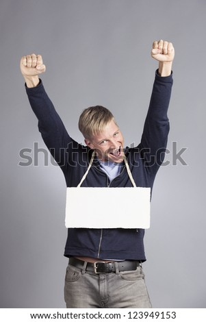 Fantastic news: Happy man with raised arms showing success and presenting white empty signboard with space for text isolated on grey background.