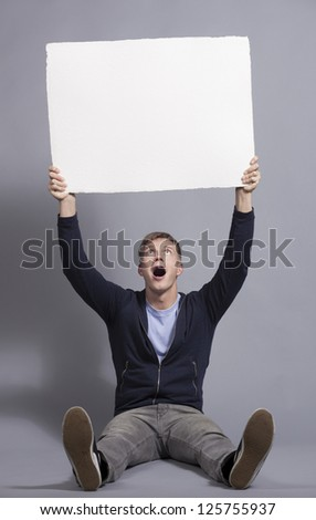 Fantastic news: Surprised friendly man holding up white blank signboard with space for text isolated on grey background.