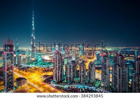 Fantastic nighttime skyline with illuminated skyscrapers. Rooftop perspective of downtown Dubai, UAE.