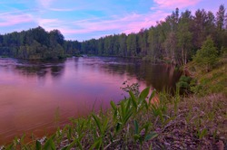 Fantastic pink sunset over the Shuya river during the white nights season. Summer landscape with the reflection of the sky in the river, green grass and forest on the high riverbank. Karelia, Russia