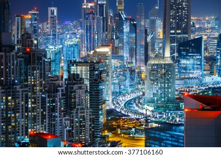 Fantastic rooftop view of illuminated city architecture by night. Business bay, Dubai, United Arab Emirates. Travel and nightlife concept. #377106160