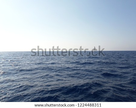 Fantastic seaside view at the sea with the lone yacht. Sailing yacht catamaran sailing in the sea. Hazey blue day at the lake watching the sailboats. Soft focus image. A little yacht sailing on sea