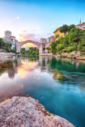 Fantastic Skyline of Mostar with the Mostar Bridge, houses and minarets, at sunset. Location: Mostar, Old Town, Bosnia and Herzegovina, Europe