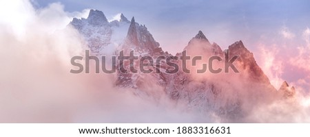 Fantastic snow mountains landscape banner background. Colorful pink and blue clouds overcast sky. French Alps, Chamonix Mont-Blanc, France