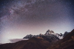Fantastic starry sky. Autumn landscape and snow-capped peaks. Main Caucasian Ridge. Mountain View from Mount Ushba Meyer, Georgia. Europe.