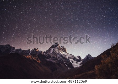 Fantastic starry sky. Autumn landscape and snow-capped peaks. Main Caucasian Ridge. Mountain View from Mount Ushba Meyer, Georgia. Europe. #489112069