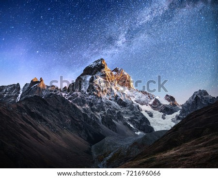Fantastic starry sky. Autumn landscape and snow-capped peaks. Main Caucasian Ridge. Mountain View from Mount Ushba Meyer, Georgia. Europe. #721696066