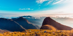 Fantastic sunrise over rocky mountain with view on misty valley. Mountain of fog. Mountain peaks. Sea of clouds. Pico Parana, Brazil. Teal and Orange.  Beautiful Brazil