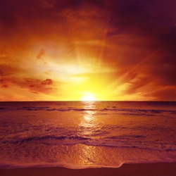 Fantastic sunset over ocean, sea waves and sand.