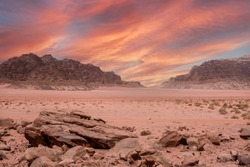 Fantastic view of the endless arid valley, Wadi Rum desert, Jordania. Spectacular sky with large red dramatic clouds, mountain range, lots of red sand and a few bushes and rocks in the background.