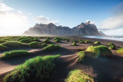 Fantastic west of the mountains and volcanic lava sand dunes on the beach Stokksness, Iceland. Colorful summer morning Iceland, Europe.