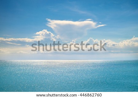 Fantastic white clouds on blue sky horizon. Calm ocean with sunlight reflection, Bali. Sunny sky clouds above blue ocean. Vibrant sunny sea and sky clouds. Amazing ocean. Tranquil Bali ocean serenity