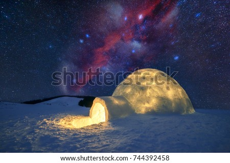 Fantastic winter landscape glowing by star light. Wintry scene with snowy igloo and milky way in night sky. Carpathian mountains. Santa house from snow,  ideal New Year and Christmas background