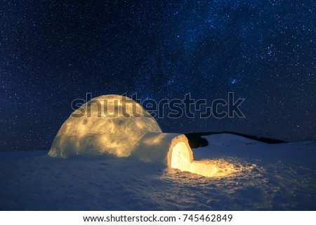 Fantastic winter landscape glowing by star light. Wintry scene with snowy igloo and milky way in night sky. Carpathian mountains. Santa house from snow,  ideal New Year and Christmas background  #745462849