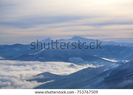 Fantastic winter landscape which including of copy-space for text. Mountains above the clouds. Ski resort Dragobrat, Carpathian mountains, Ukraine.