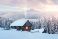 Fantastic winter landscape with wooden house in snowy mountains. Smoke comes from the chimney of snow covered hut. Christmas holiday and winter vacations concept