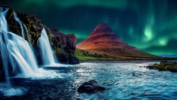 Fantastic winter scenery. Kirkjufell mountain with beautiful aurora borealis and frozen water falls in winter, Iceland. One of the famous natural heritage in Iceland. Incredible Nature landscape