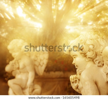 Fantastical portrait of angelic cherub statues with rays of golden light