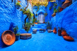 Fantastically beautiful moroccan courtyard in Chefchaouen blue city medina in Morocco with blue walls, architectural details, colorful flower pots and household items