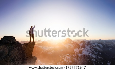 Fantasy Adventure Composite with a Man on top of a Mountain Cliff with Dramatic Landscape in Background during Sunset or Sunrise. Landscape from British Columbia, Canada.
